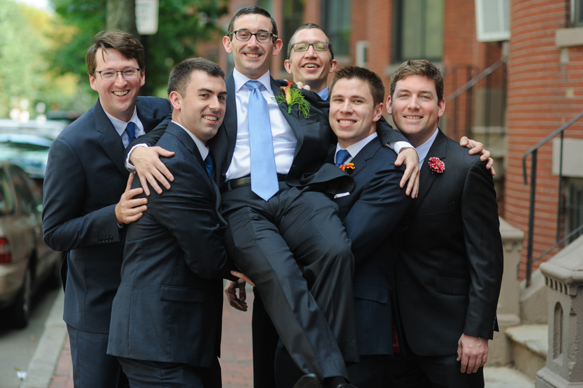 groomsmen holding up groom at his wedding
