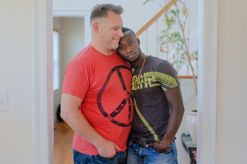 casual intimate gay couple engagement in home