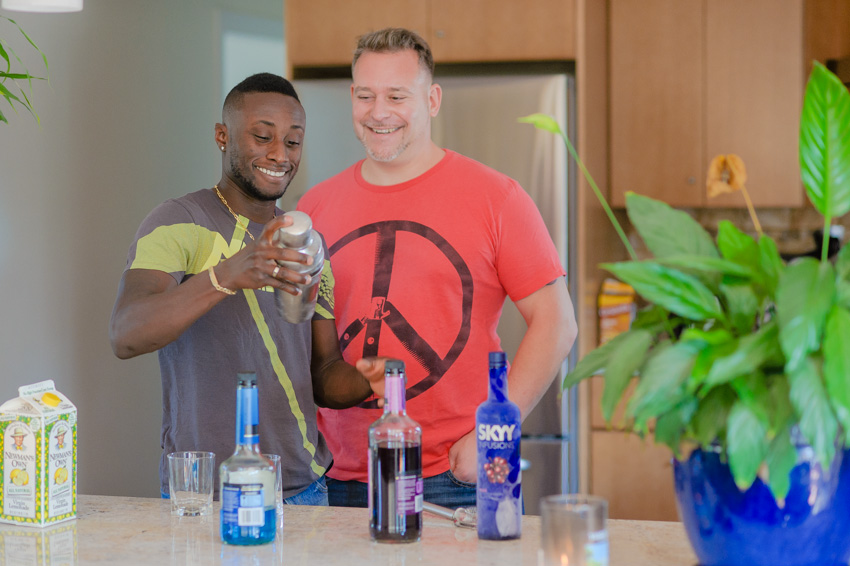 same-sex couple making a alcoholic beverage at home