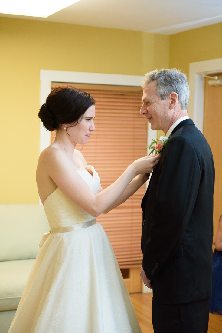 bride pins boutonniere on father